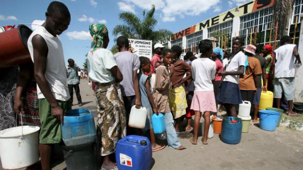 Menschen stehen mit Behältern Schlange vor einem Wassertank.