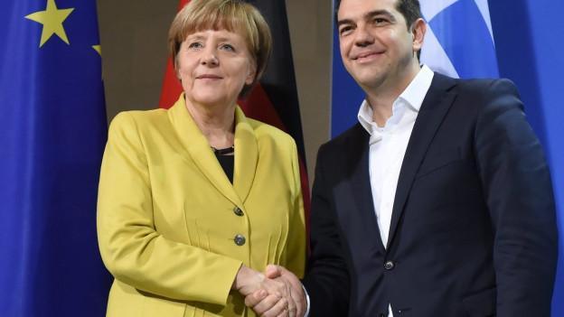 Deutsche Kanzlerin und griechischer Regierungs-Chef lächelnd, einander die Hände schüttelnd.