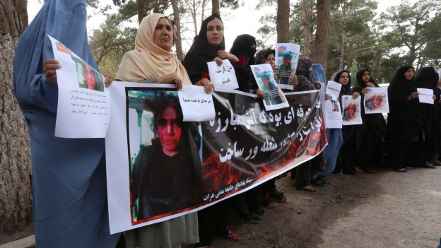 Verschleierte Frauen halten Bild einer Ermordeten hoch.
