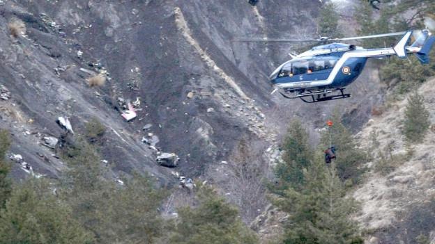 Ein Helikopter mit Rettungsseil über graubraunen Schutthängen.