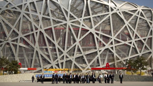 Das Bild zeigt gross das Nationalstadion in China, das Vogelnest. Davor - nur ganz klein sichtbar - die Mitglieder des olympischen Komitees IOC.