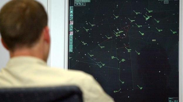 Mann von hinten, der vor Bildschirm mit Flugdaten sitzt.