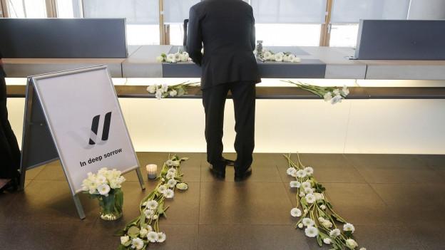 Aufnahme eines Mannes, der ins Kondolenzbuch der Lufthansa schreibt, auf dem Boden liegen Blumen.