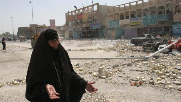 Aufnahme einer verhüllten Frau in Bagdad, vor einem zerstörten Gebäude.