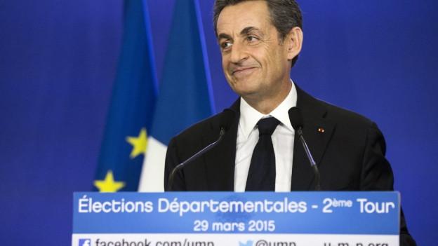 UMP-Chef Sarkozy lächelnd an einem Redner-Pult vor blaubem Hintergrund.