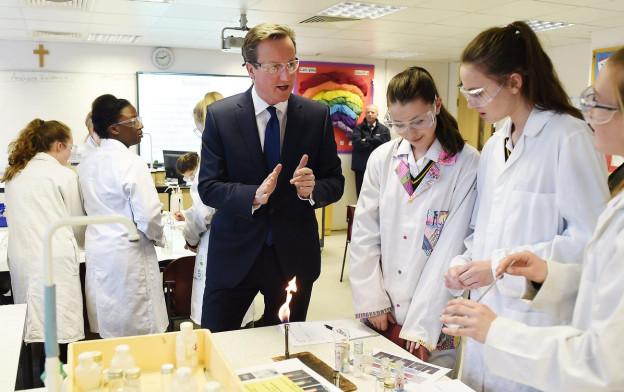 Aufnahme des britischen Premierminister David Cameron bei einem Besuch einer Mädchenschule in London, er trägt eine Schutzbrille, vier Mädchen um ihn herum tragen weisse Schutzkleider.
