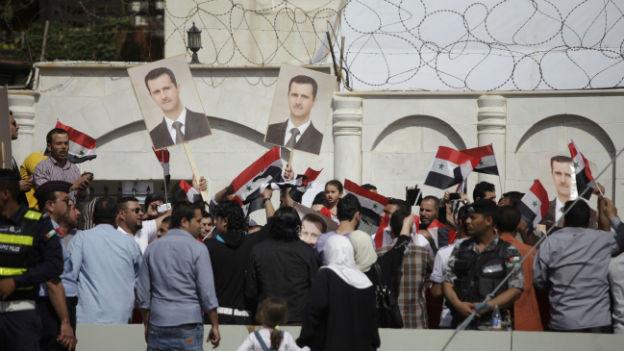 Menschenmasse mit Assad-Plakaten, im Hintergrund Stacheldraht