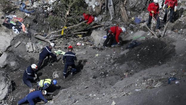 Menschen in Bergbekleidung in felsigem Terrain, verstreute Trümmerteile.