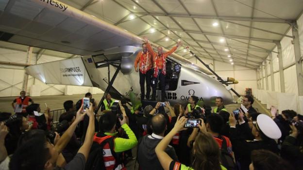 Zwei Männer vor Solarflugzeug, umringt von applaudierenden Menschen.