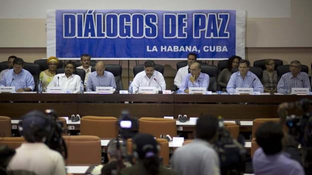 Aufnahme eines Podiums in einem Verhandlungssaal in Kuba, wo Vertreter der kolumbianischen Regierung und der FARC vor den Medien auftreten. Im Hintergrund ein Plakat mit der Inschrift «Friedensgesprächs» in Spanisch.
