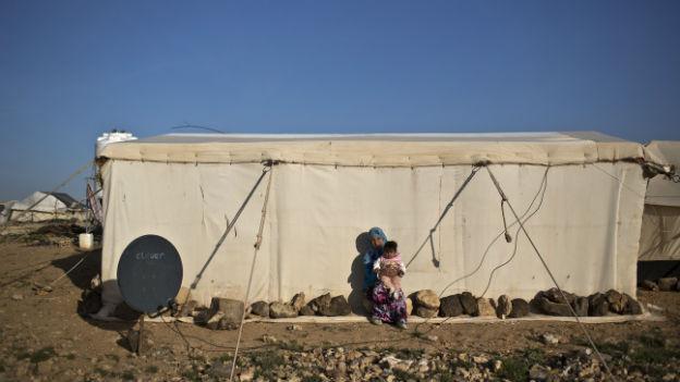 Eine Frau hält ihr Kind im Arm vor einem Zelt in einem Flüchtlingslager.