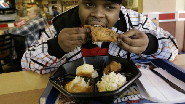Ein Mann isst ein fritiertes Hähnchen bei KFC.
