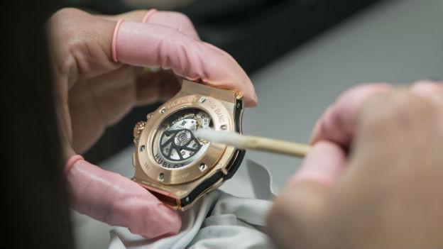 Finger halten eine wertvolle Uhr und säubern Teile.