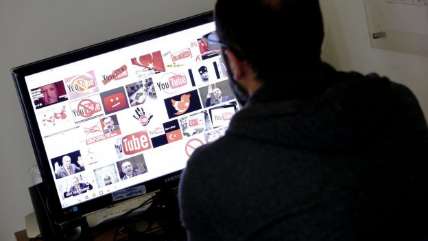 Mann vor Computer (auf Bildschirm Social-Media-Symbole).
