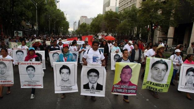Aufnahme eines Protestzuges in einer Strasse, die Menschen halten grosse Fotos der vermissten Studenten hoch.