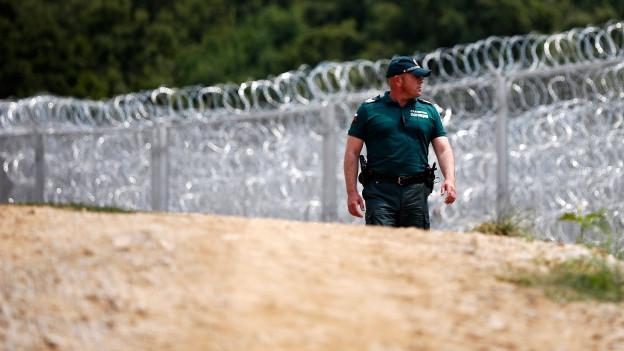 Ein bulgarischer Grenz-Polizist kontrolliert die bulgarisch-türkische Grenze vor dem hochmodernen Stacheldrahtzaun.
