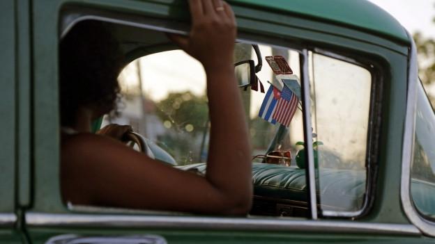 Blick in die Fahrerkabine eines alten kubanischen Taxis: Über dem Armaturenbrett hängen kleine kubanische und amerikanische Flaggen.