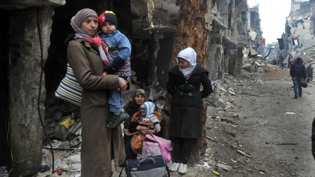 Zwei Frauen mit Kleinkindern und ein Mädchen warten am Strassenrand, im Hintergund Ruinen und palästinensische Flaggen.