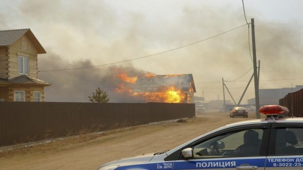 Aufnahme eines brennenden Hauses in einem sibirischen Dorf, im Vodergrund ein parkiertes Polizeiauto.