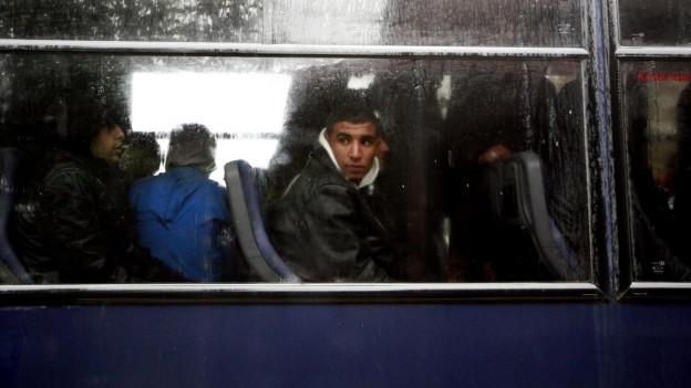 Zu sehen ist ein stehender Bus, durch die Scheiben sieht man Flüchtlinge warten