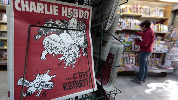 Ein Kiosk in Nizza, im Vordergrund ist eine Ausgabe von Charlie Hebdo zu sehen: Karikaturen von verschiedenen Personen.