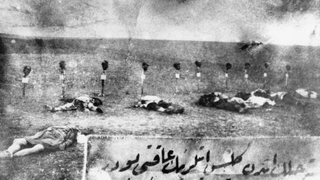 Historisches schwarzweiss Foto von 1915: mehrere tote Körper liegen auf einem Feld.