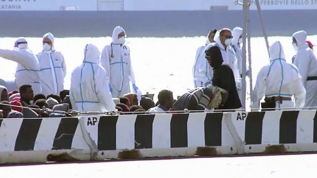Mitarbeiter der Küstenwache betreuen die Flüchtlinge