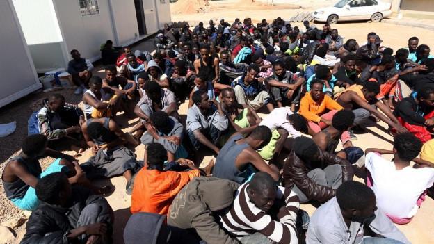 Schwarzafrikaner kauern auf einem Platz (im Hintergrund Baracken).