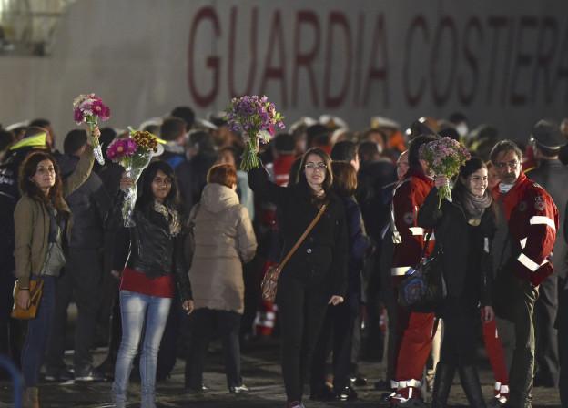 Eine Gruppe von Menschen im Scheinwerferlicht mit Blumensträussen in den Händen.