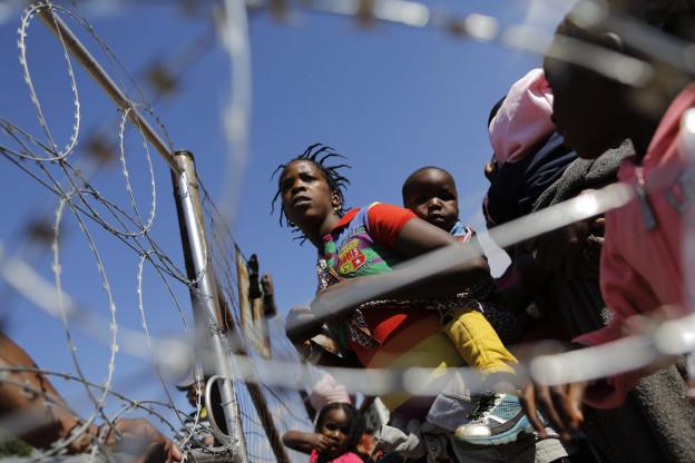 Eine schwarze Frau mit einem Kind auf dem Rücken vor einem Stacheldrahtzaun.