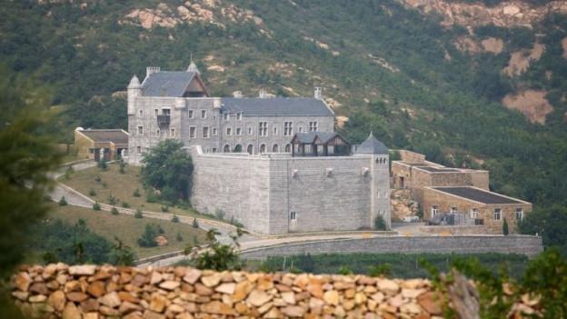 Ein neu gebautes Schloss an einem Berghang.