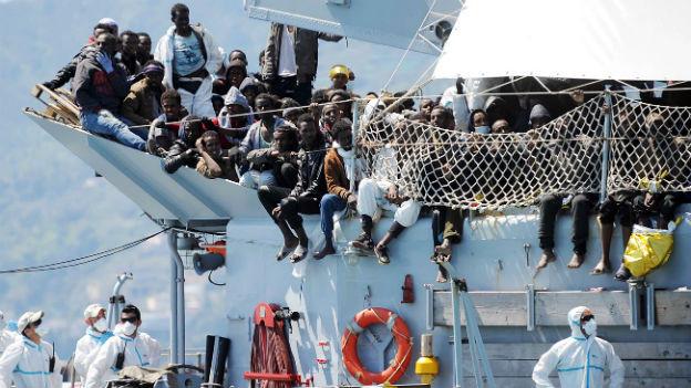 Flüchtlinge sitzen auf dem Deck eines italienischen Armee-Schiffes im Hafen von Salerno.