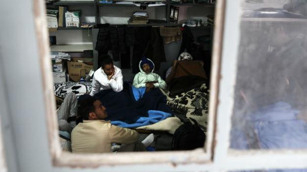 Flüchtlinge sitzen am Boden in einem Lagerraum der griechischen Küstenwache.