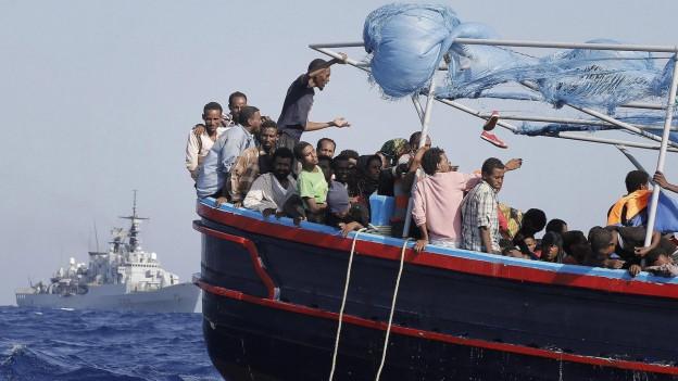 Gerettete Flüchtlinge vor einem italienischen Marine-Schiff am 12. September 2014.