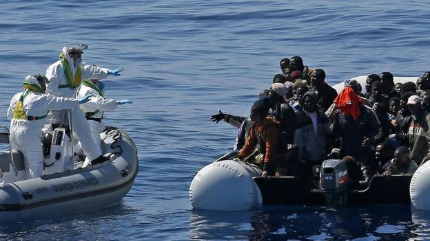 Zwei Schlauchboote nahe beieinander im Wasser. Auf dem linken stehen drei Männer in weissen Schutzanzügen, auf dem anderen ein dutzend Flüchtlinge.