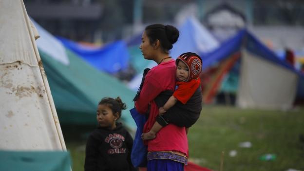 Eine Frau mit einem Kleinkind im Tragetuch, daneben steht ein weiteres Mädchen. Im Hintergrund sind Zeltplanen zu sehen.