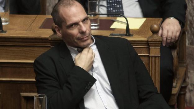 Mann im Parlamentsstuhl, greift sich an den Kragen.