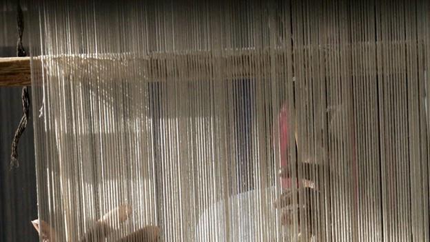 Ein Mann in Nepal knüpft einen Teppich