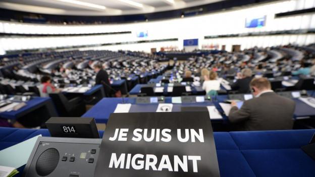 Aufnahme des EU-Parlaments und einem Schild, das Solidarität mit den Flüchtlingen bekundet.