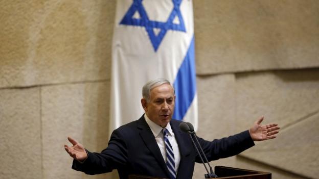 Das Bild zeigt Premier Netanjahu hinter einem Rednerpult auf einem Podium - im Hintergrund ein blaues Plakat mit grosser hebräischen Schriftzeichen..