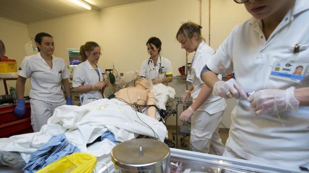 Auf dem Bild sind fünf Frauen zu sehen, die in einem Spitalzimmer Simulationstests durchführen, im Rahmen ihrer Ausbildung.