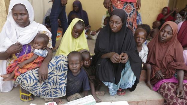 Auf dem Bild sind befreite Frauen und Kinder zu sehen, die am Boden sitzend, in einem Flüchlingscamp notversorgt werden.