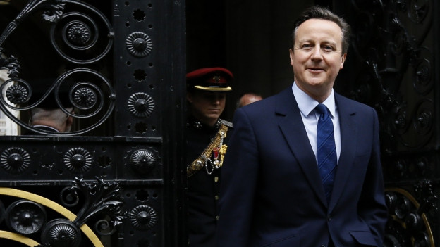 Der neugewählte Premier Cameron schreitet durch ein schmiedeisernes Tor.