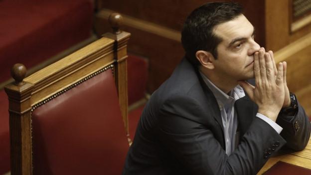 Alexis Tsipras hört einer Rede zu in Athen und stützt dabei Kopf auf seinen Händen ab.