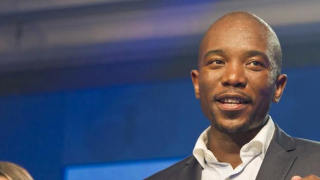 Portraitaufnahme von Mmusi Maimane vor einem blauen Hintergrund.