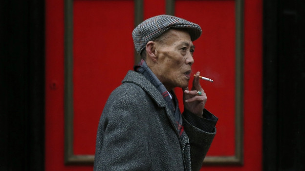 Ein älterer chinesischer Herr mit einer brennenden Zigarette spaziert an einer roten Tür vorbei.