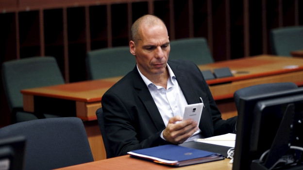 Finanzminister Varoufakis sitzt alleine in einem Verhandlungsraum und tippt etwas in sein Smartphone.