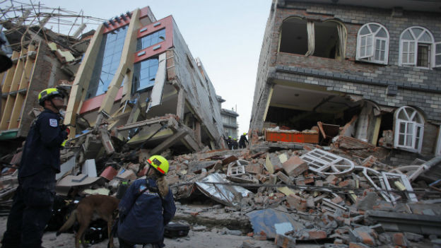 Helfer stehen vor einem zerstörten Geschäftsgebäude.