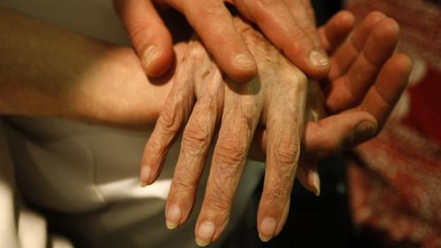 Aufnahme von Händen einer alten Person, die von einer jüngeren Person massiert werden.