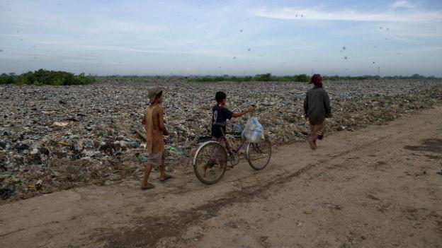 Drei jünge Männer laufen auf einem Pfad, der durch eine Mülldeponie führt.